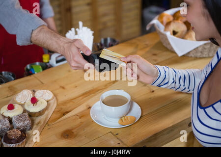 Woman making payment through credit card at counter in café - Stock Photo