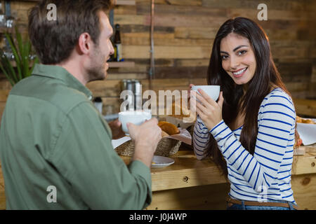 Portrait of woman having coffee at counter in café - Stock Photo