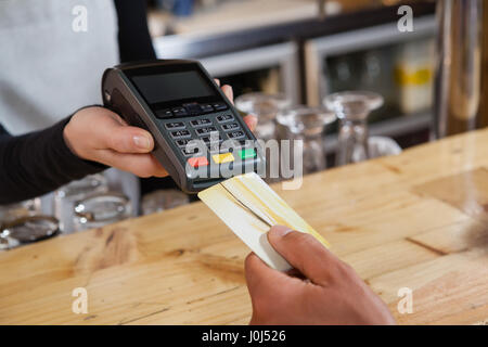 Cropped image of person making payment at cafe shop - Stock Photo