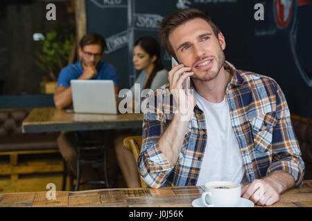 Man talking on mobile phone while having coffee in café - Stock Photo