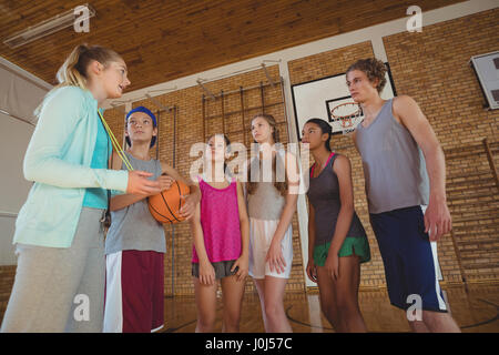 Female coach mentoring high school kids in basketball court - Stock Photo