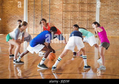 Determined high school kids warming up in the court - Stock Photo