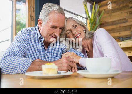 Happy senior couple embracing each other in café - Stock Photo