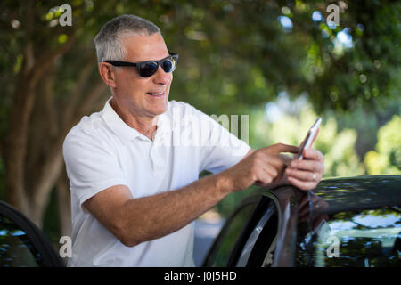 Smiling senior man using smart phone while standing by car - Stock Photo