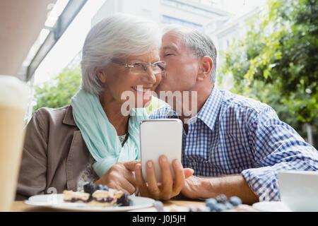 Senior man kissing woman in outdoor café - Stock Photo