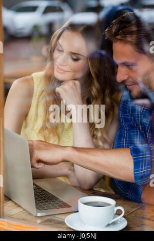 Couple using digital laptop while sitting at cafe shop seen through glass window - Stock Photo