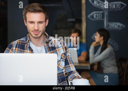 Man using laptop while having coffee in café - Stock Photo