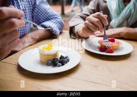 Senior couple having cupcake with blueberries and blackberries in outdoor café - Stock Photo