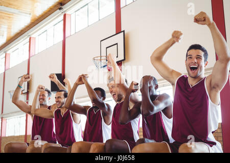 Excited basketball player sitting on bench in court