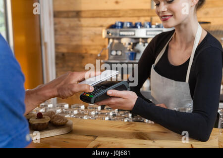 Close up of man making payment on credit card reader machine at cafe shop - Stock Photo
