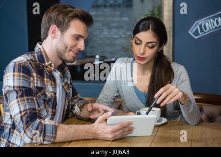 Young couple using digital tablet while having coffee in café - Stock Photo