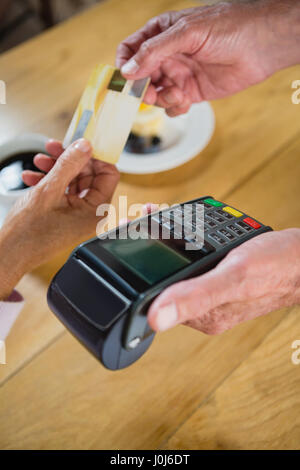 Senior woman making payment through credit card in café - Stock Photo