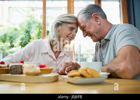 Romantic senior couple sitting together in café - Stock Photo