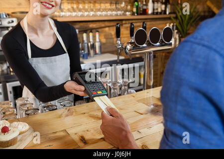 Man making payment on credit card reader machine at cafe shop - Stock Photo
