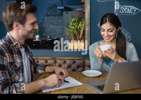 Young couple interacting while having coffee in café - Stock Photo