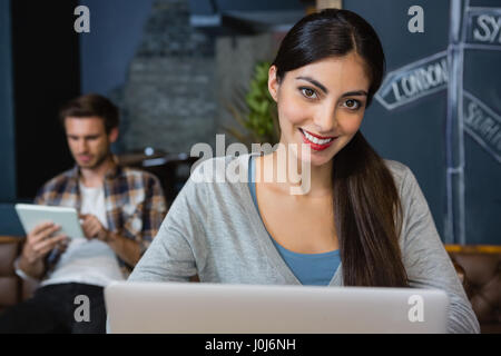 Portrait of young woman using laptop in café - Stock Photo