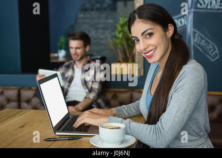 Portrait of young woman using laptop while having coffee in café
