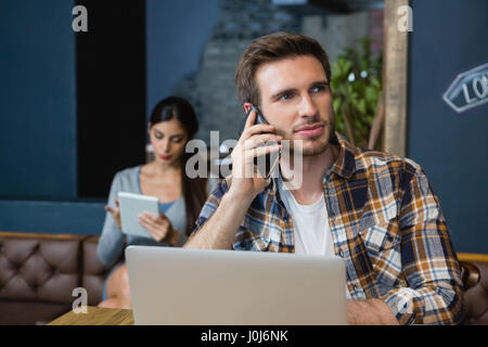 Young man talking on mobile phone while using laptop in café - Stock Photo