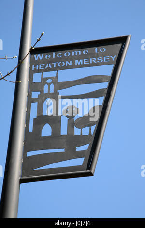 Iron work road sign on lamp post 'Welcome to Heaton Mersey' village between Didsbury and Stockport in Greater Manchester - Stock Photo