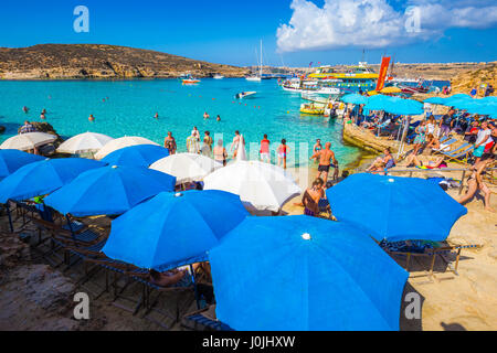 BLUE LAGOON, COMINO, MALTA - October 18, 2016: Tourists crowd to enjoy the clear turquoise water under umbrellas - Stock Photo