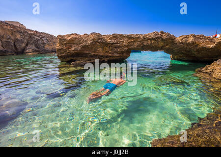 Blue Lagoon, Malta - Snorkeling tourist at the caves of the Blue Lagoon on the island of Comino on a bright sunny - Stock Photo