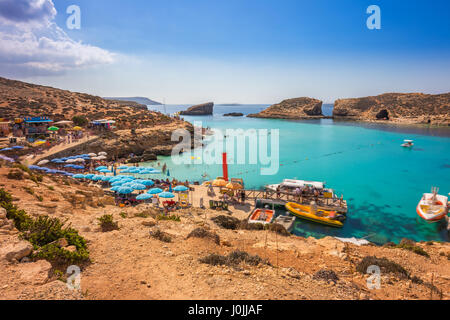 Comino, Malta - Tourists crowd at Blue Lagoon to enjoy the clear turquoise water on a sunny summer day with clear - Stock Photo