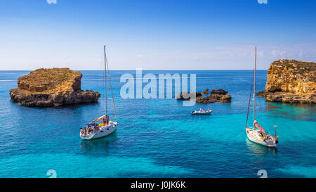 Comino, Malta - Sailing boats at the beautiful Blue Lagoon at Comino Island with turquoise clear sea water, blue - Stock Photo