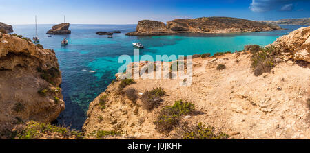 Comino, Malta - The beautiful Blue Lagoon with turquoise clear sea water, yachts and snorkeling tourists on a sunny - Stock Photo