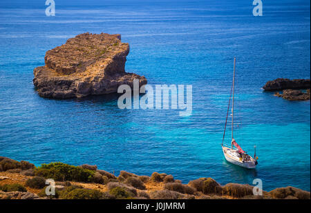 Blue Lagoon, Malta - Sailing boat at the famous Blue Lagoon at the Island of Comino on bright sunny summer day with - Stock Photo