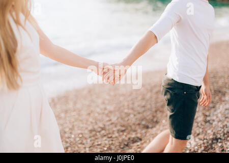 Newlyweds hold hands on the sea. Couple holding hands. Wedding in Montenegro. - Stock Photo