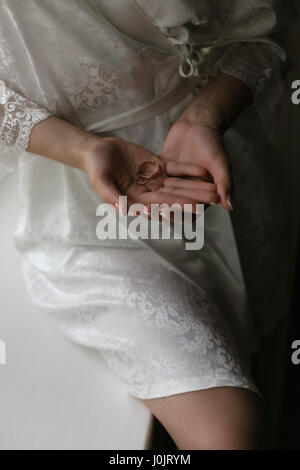 Wedding rings in the hands of the bride in a white dressing gown - Stock Photo