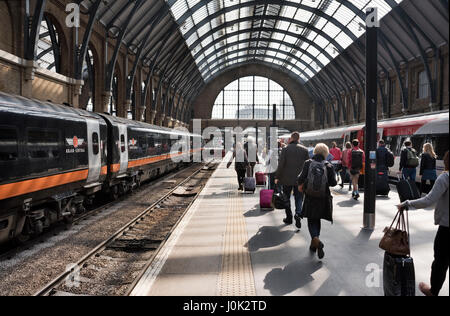 Passengers arriving at  King's Cross railway station, London, UK - Stock Photo