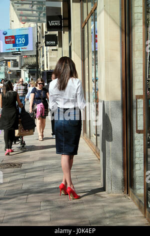 Back view of attractive slender woman with long brunette hair standing outside in a street texting in red high heels - Stock Photo