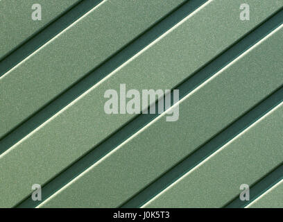 Greenery metallic fence made of corrugated steel sheet with vertical guides. Corrugated green iron sheet background - Stock Photo