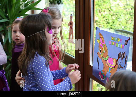 Children blind folded playing pin the tail on the Donkey at a birthday party games concept, childhood fun, joy, - Stock Photo