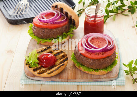 Burger with lettuce tomato red onion on grilled buns with ketchup - Stock Photo