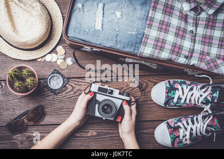 Travel background with open suitcase and accessories. Top view - Stock Photo