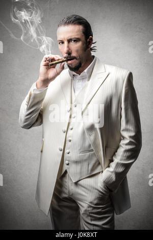 Elegant man smoking cigar - Stock Photo