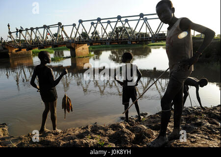 SOUTH SUDAN Lakes state, Rumbek, boys catching fish at Bamam bridge, which was destroyed during the war between - Stock Photo