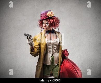 Clown woman with pistol - Stock Photo