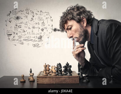 Businessman playing chess and making a plan - Stock Photo