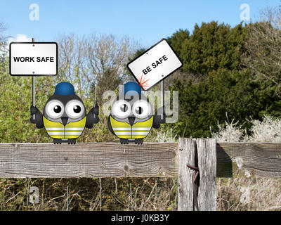 Comical construction workers with health and safety work safe be safe message perched on a countryside fence - Stock Photo