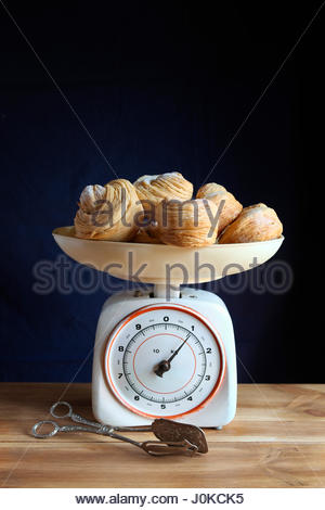 Baked cruffins on a vintage kitchen scale with silver plated serving tong - Stock Photo