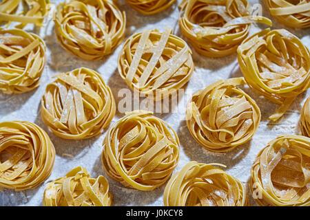 Fresh pasta with flour on white surface - Stock Photo