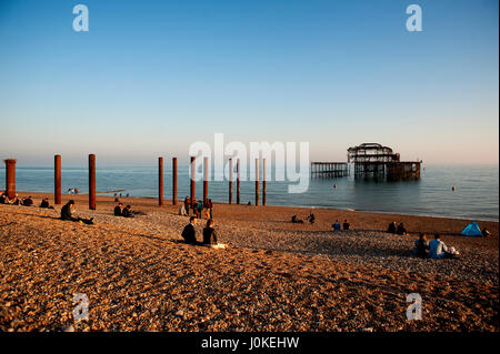 People sit on the pebble beach at Brighton's West Pier a famous landmark on the south coast of England, now a burnt - Stock Photo