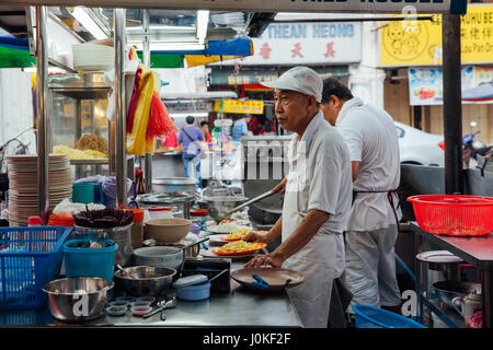 George Town,  Malaysia - March 22, 2016: Senior man sells noodles at the Kimberly Street Food Night Market on March - Stock Photo