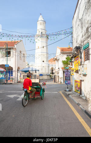 George Town,  Malaysia - March 21, 2016: Cycle rickshaw is riding down the street in front of the Lebuh Aceh Mosque. - Stock Photo