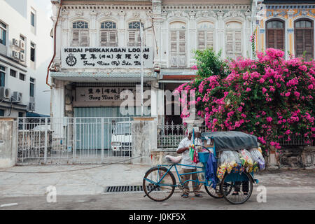 George Town,  Malaysia - March 22, 2016: Vendor sells snacks from the tricycle in UNESCO Heritage buffer zone in - Stock Photo