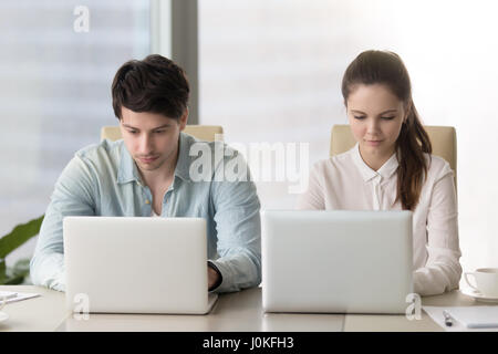 Male and female office workers. Focused on working with laptops - Stock Photo