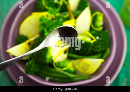 Closeup of spoon with vinaigrette over pear, broccoli, green beans salad - Stock Photo